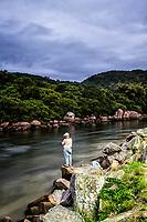 Homem idoso em pé sobre pedra no Canal da Barra da Lagoa. Florianópolis, Santa Catarina, Brasil. / Elder man standing on a rock at Barra da Lagoa Canal. Florianopolis, Santa Catarina, Brazil.