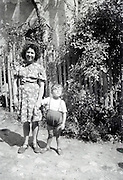 mother posing with little child countryside in front of a building