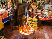 30 JANUARY 2014 - BANGKOK, THAILAND:   A woman burns offerings to appease the Gods during Lunar New Year festivities, also know as Tet and Chinese New Year, in Bangkok. This year is the Year of the Horse. Ethnic Chinese make up about 14% of Thailand and Chinese holidays are widely celebrated in Thailand.     PHOTO BY JACK KURTZ