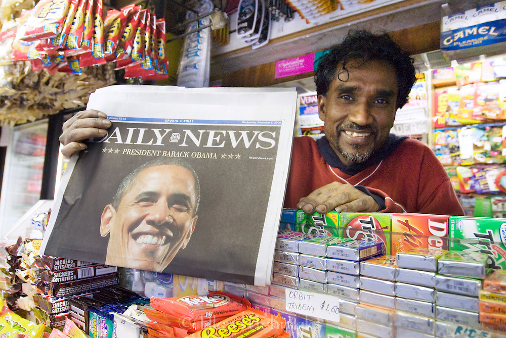 Proud newsstand owner in New York City, holding up a newspaper announcing Barack Obama's historic presidential win in November, 2008