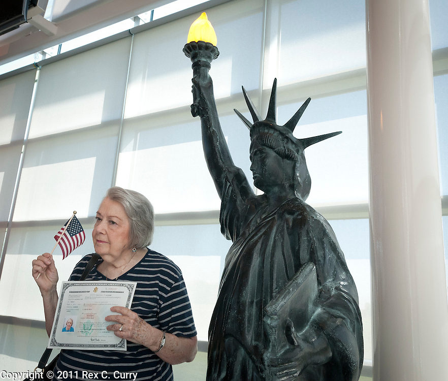Edith Smith poses next to a replica of the Statue of Liberty after a naturalization ceremony at the USCIS office in Irving on June 30, 2011. She has been in the U.S. with a permanent resident card for 47 years. She originally is from Norway via Argentina.