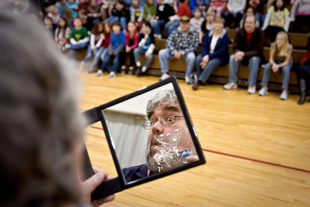 "JEROME A. POLLOS/Press..John Klapp, a teacher at Seltice Elementary, puts the finishing touches on his ""half shave"" during a school assembly Tuesday where four staff members at the school shaved half of their facial hair after the school raised $505 for Haitian earthquake victims. Klapp hadn't shaved since Dec. 23."