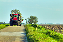 Farmer pulling an implement down a remote blacktop road in central Illinois