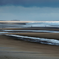 Storm clouds over the vast beach at Holkham, north Norfolk with two silhouetted figures in the distance walking towards the white surf