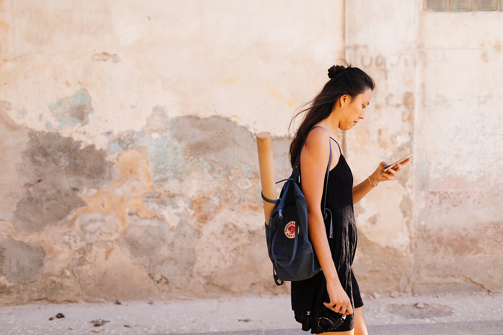 20 something uses cell phone GPS to find her way in Old Havana, Havana Cuba