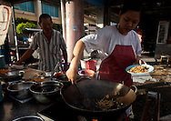 serving char koey teow, rice noodles fried with shrimp and bean sprouts, george town,penang, malaysia.many george town vendors still cook over charcoal as does this couple on kimberly street.