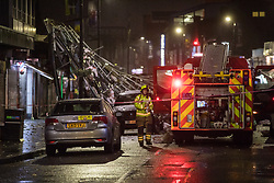 Slough, UK. 14 January, 2020. A large section of roof lies in the middle of Slough High Street after being blown off the top of a block of flats as Storm Brendan hit the town. Emergency services responded to the incident and a police officer on the scene reported that there had been no injuries.