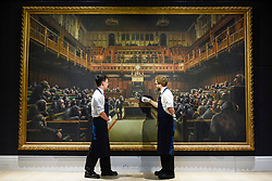 "© Licensed to London News Pictures. 27/09/2019. LONDON, UK. Technicians present ""Devolved Parliament"", 2009, by Bansky (Est. GBP1.5-2m). Preview of Sotheby's Frieze Week Contemporary Art exhibition at its New Bond Street galleries.  Over 250 works by artists, including Andy Warhol, David Hockney and Jean-Michel Basquiat, will be auctioned on 3 October 2019.  Photo credit: Stephen Chung/LNP"