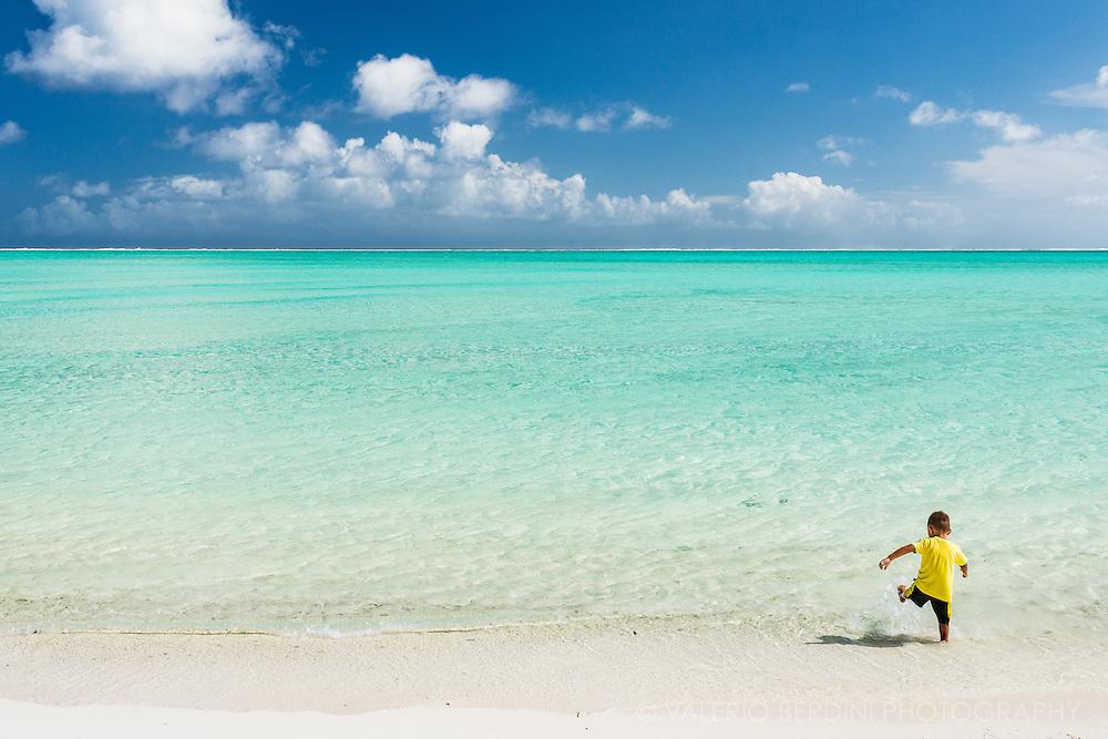 A polynesian kid plays on the sand of Matira beach in Bora Bora