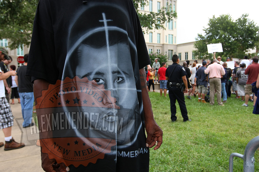 A pro-Trayvon demonstrator wears a t-shirt that bears a resemblance to George Zimmerman with a rifle scope pattern centered on his head, in the peaceful protest area, prior to the trial of George Zimmerman at the Seminole County Courthouse, Saturday, July 13, 2013, in Sanford, Fla. Zimmerman had been charged for the 2012 shooting death of Trayvon Martin. Zimmerman was found not guilty by a jury of six women. (AP Photo/Alex Menendez)