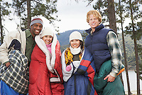 Four young adults wrapped in sleeping bags standing by lake
