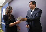 DES MOINES, IA - OCTOBER 25, 2013: Senator Ted Cruz, Republican of Texas, hands a signed program to Sarah Brooks (left), 19, of Des Moines, Iowa before the start of the Iowa GOP Ronald Reagan Dinner at the Iowa Events Center - Community Choice Credit Union Convention Center in Des Moines, Iowa.