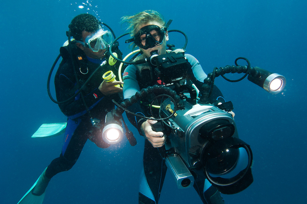 Diver with a video camera housing and lights, Manokwari, West Papua, Indonesia.