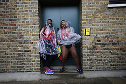 © Licensed to London News Pictures. 28/08/2016. London, UK. Dancers take shelter from the rain whilst parading on family day of Notting Hill Carnival in west London, Sunday, 28 August 2016. Photo credit: Tolga Akmen/LNP