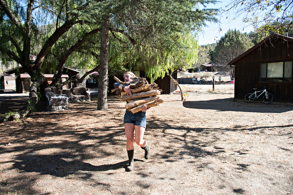 LOS OLIVIOS, CA - OCTOBER 21, 2016:  <br /> <br /> Sophomore Emily Cummings, 15, chopped wood she helped to collect over the weekend for the fires that will heat her grade's afternoon shower. Grabbing a huge pile of the newly chopped wood, Cummings carries it to the water heater to build a fire. The Midland School, a place-based college prep boarding school in Los Olivos, Calif., has built the teachings of wants vs. needs into the very center of their curriculum. Basic needs like electricity, hot water and food are a big part of the kids' responsibilities. In order to have hot water for their showers, the kids have to collect wood, chop it and build fires each day in water heaters that each grade has for its showers. <br /> <br /> (Melissa Lyttle for The New York Times)