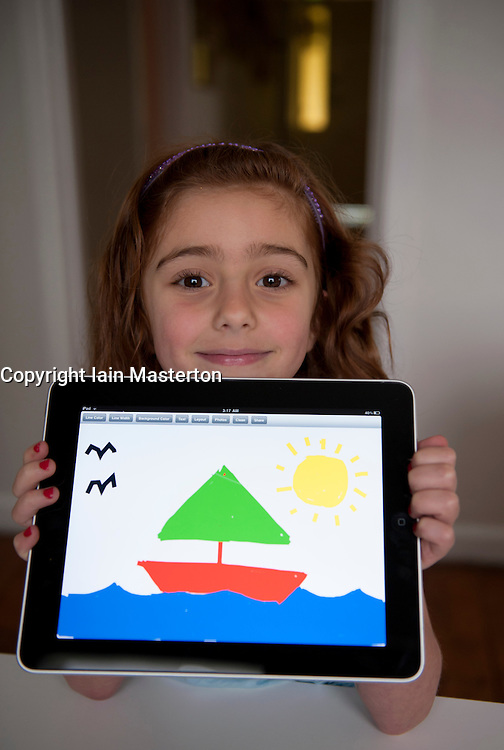 Young girl showing her drawing made on painting application on an iPad tablet computer