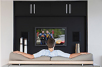 Back view of mid-adult man watching television in living room