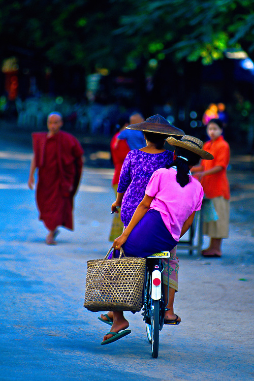 Burmese women riding bicycle, Mandalay, Burma (Myanmar)