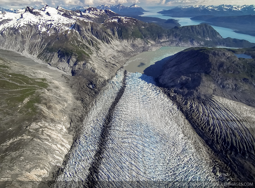 This aerial view shows the last portion of the McBride Glacier before it meets the ocean in Glacier Bay National Park and Preserve. The McBride Glacier is the most active glacier and only tidewater glacier in the Muir Inlet, is retreating. Muir Inlet can be seen in the upper right of the photo.<br /> <br /> The dark line of rock debris is called called a medial moraine. A medial moraine is formed when two glaciers meet and the debris on the edges of the adjacent valley sides join and are carried on top of the glacier.<br /> <br /> Glacier Bay National Park is located in southeast Alaska. Known for its spectacular tidewater glaciers, icefields, and tall costal mountains, the park is also an important marine wilderness area. The park a popular destination for cruise ships, is also known for its sea kayaking and wildlife viewing opportunities. <br /> <br /> Glacier Bay National Park is home to humpback whales which feed in the park's protected waters during the summer, both black and grizzly bears, moose, wolves, sea otters, harbor seals, steller's sea lions and numerous species of sea birds. <br /> <br /> The dynamically changing park, known for its large, contiguous, intact ecosystems, is a United Nations biosphere reserve and a UNESCO World Heritage site.