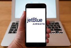 Using iPhone smartphone to display logo of jetBlue airlines a budget carrier in the USA