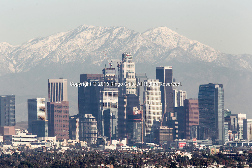 After the back to back storms, snow covered the San Gabriel Mountains are seen above the downtown Los Angeles skyline Jan., 12, 20016. Much of the Southland will be under a ``no-burn'' order tomorrow, meaning indoor fireplace use and outdoor wood burning will be prohibited due to pollution concerns. The South Coast Air Quality Management District issued the order for all residences in the South Coast Air Basin, including the greater Los Angeles area, Orange County and the Inland Empire.  The order excludes the Coachella Valley, residences above 3,000 feet in elevation, and homes where there is no other source of heat. Fine particles in wood smoke can penetrate deep into lungs, causing problems for people with asthma or other respiratory disorders.(Photo by Ringo Chiu/PHOTOFORMULA.com)<br /> <br /> Usage Notes: This content is intended for editorial use only. For other uses, additional clearances may be required.