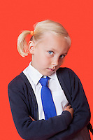 Portrait of a young schoolgirl with arms crossed over orange background