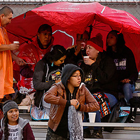 Fan huddle underneath umbrellas and rain coats to wait a a ran delay at Tohatchi High School Friday.