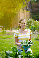 Young Woman Holding Colander Filled with Spinach Leaves Outdoors