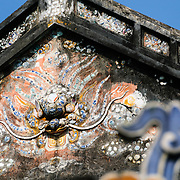 Decorative art on a building at the Imperial City in Hue, Vietnam. A self-enclosed and fortified palace, the complex includes the Purple Forbidden City, which was the inner sanctum of the imperial household, as well as temples, courtyards, gardens, and other buildings. Much of the Imperial City was damaged or destroyed during the Vietnam War. It is now designated as a UNESCO World Heritage site.