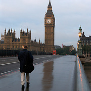 Man walking across the Westminster Bridge toward Big Ben and the Houses of Parliament and the Palace of Westminster, London, England, UK<br />
