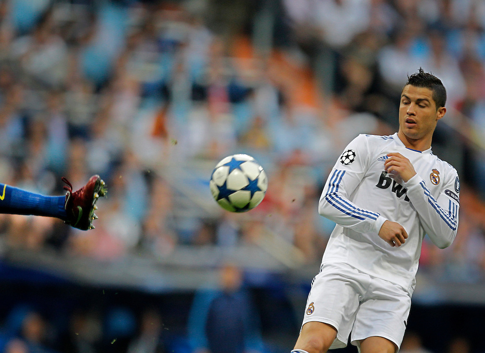 Real Madrid's Cristiano Ronaldo from Portugal, right, vies for the ball with Barcelona player during their semi final, 1st leg, Champions League soccer match at the Santiago Bernabeu stadium in Madrid, Wednesday, April 27, 2011.