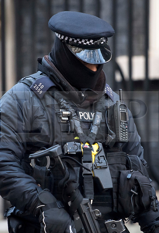 © Licensed to London News Pictures. 08/12/2017. London, UK. An armed price officer heavily wrapped up in bitterly cold weather on Downing Street in London. Temperatures across Britain have dropped over night wit many areas hit by snow. Photo credit: Ben Cawthra/LNP