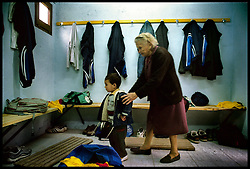 Girona, Catalunya, Spain<br /> A grandmother with her grandchild in the looker room at the football field in Argelaguer.<br /> &copy;Carmen Secanella.