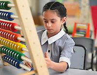Schoolgirl using abacus in classroom