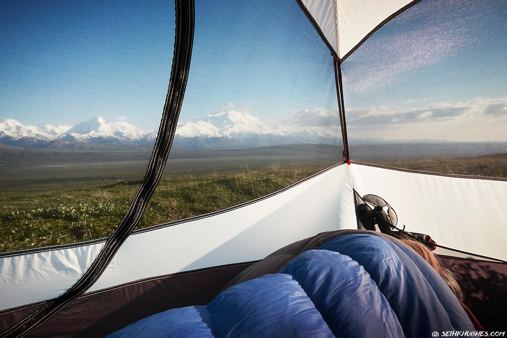 A woman sleeps inside her tent while backcountry camping near Mt. McKinely in Denali National Park, Alaska.
