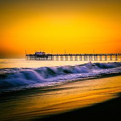 Balboa Pier picture at sunset in Orange County California. Balboa Pier is in Newport Beach on Balboa Peninsula  along the Pacific Ocean in Orange County Southern California. The pier is a popular attraction for fishing and the Ruby's Diner restaurant at the end of the pier.