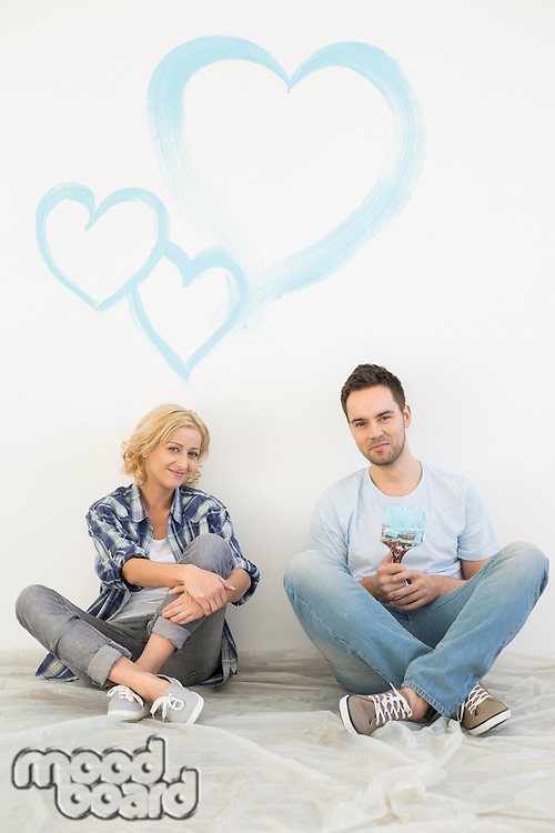 Full-length portrait of mid-adult couple with painted hearts on wall