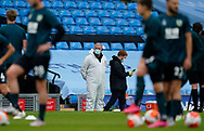Men in masks and protective suits wait on the touchlines as the players warm up during the Premier League match at the Etihad Stadium, Manchester. Picture date: 22nd February 2020. Picture credit should read: Andrew Yates/Sportimage