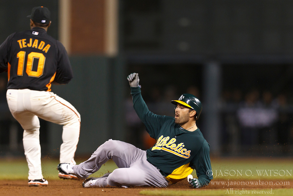 March 28, 2011; San Francisco, CA, USA;  Oakland Athletics center fielder David DeJesus (12) slides into second base in front of San Francisco Giants shortstop Miguel Tejada (10) for a double during the eighth inning at AT&T Park.