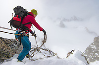 A female mountaineer holds a climbing rope on the ridge of Aigille Marbrees on a cloudy winter day.