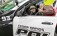 Carter Beckman (from left), 6, looks up at his mother, Kelly Beckman, of Cedar Rapids, as he sits in a police car on display at the Downtown Farmers' Market in Cedar Rapids on Saturday morning, June 2, 2012. There were 244 vendors who participated in the first market of the year. (Stephen Mally/Freelance)