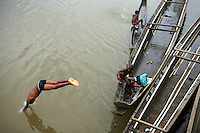 A boy dives into the Atrato River in Quibdo, the capital of the state of Choco, on October 10, 2006. Choco is a state that has suffered terribly at the hands of both rightwing paramilitaries and leftist rebels over the years, causing many to flee to other parts of Colombia. The Choco is located on the Pacific coast of Colombia and most of the people are black descendants of African slaves. (Photo/Scott Dalton)..