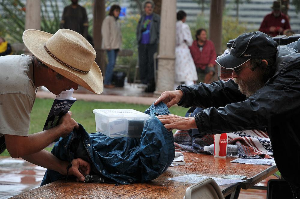 Protecting sound engineering gear from the rainstorm at Courtyard Stage, 2010 Tucson Folk Festival. Event photography by Martha Retallick.