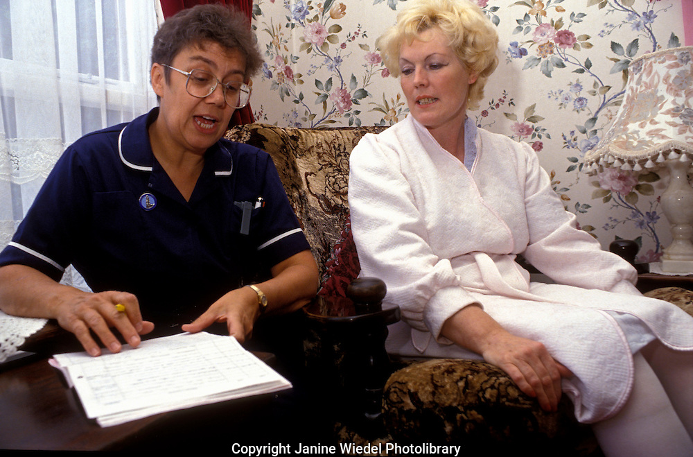 District nurse visiting woman in her home woman while recovering from operation  as part of Hospital at Home scheme.