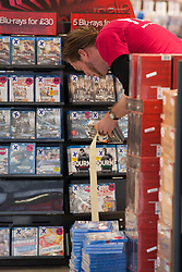 © Licensed to London News Pictures . 11/01/2013 . Belfast , UK . A staff member marks blu-ray discs with blue cross stickers at an HMV branch in Belfast , UK today (11th January 2013) as the chain announces a 25 percent off blue cross sale . Photo credit : Joel Goodman/LNP.