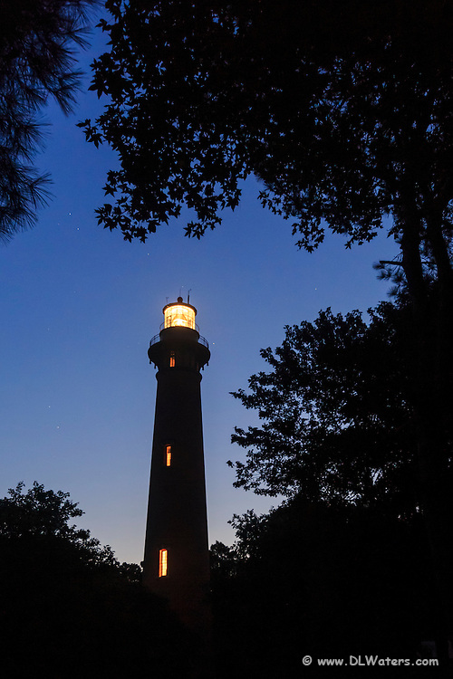 Trees frame  the Currituck Beach Lighthouse at twilight in Corolla on the Outer Banks.