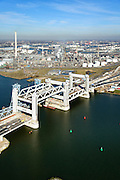 Nederland, Zuid-Holland, Rotterdam, 18-02-2015; bouw van de nieuwe Botlekbrug. De brug over de Oude Maas is een hefbrug, een van de twee brugdelen in geheven toestand. De heftorens van de oude brug gaan verscholen achter de nieuwe brug. Shell raffinaderij Pernis in de achtergrond.<br /> Construction of the new Botlek bridge.<br /> The bridge over the Oude Maas is a vertical-lift bridge or lift bridge, one of the two bridge sections raised. <br /> luchtfoto (toeslag op standard tarieven);<br /> aerial photo (additional fee required);<br /> copyright foto/photo Siebe Swart