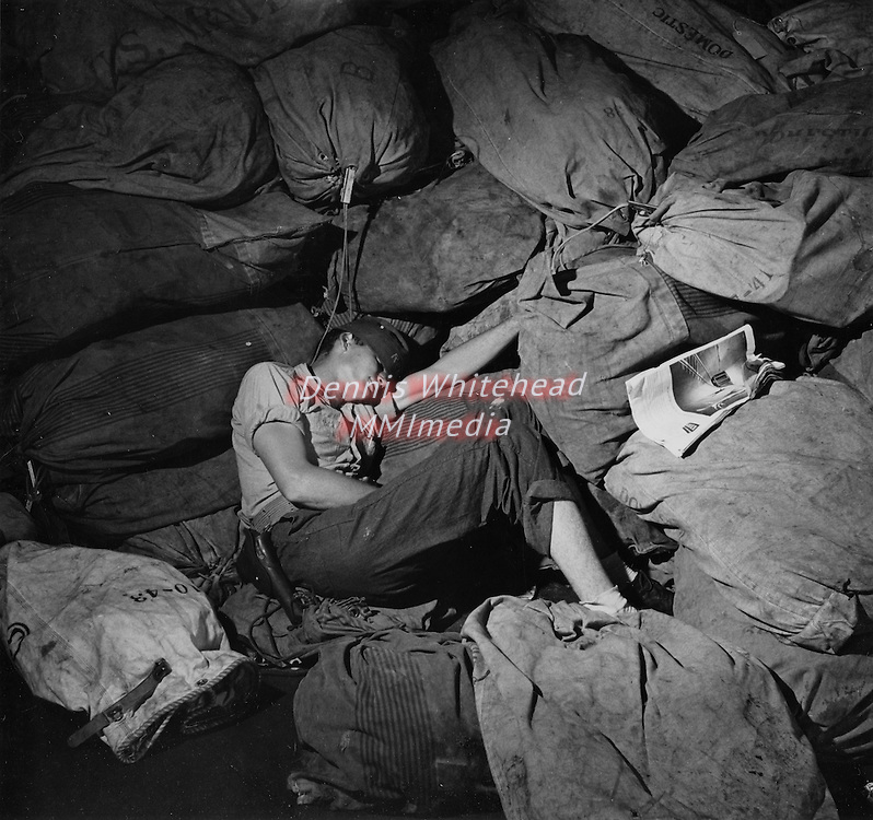 December 1944 - A sailor naps amid the mailbags on board the USS New Jersey