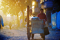 China, Datong, 2003. Street vendors head toward busier thoroughfares as the sun sets in Datong, an industrial city in northern Shanxi Province..