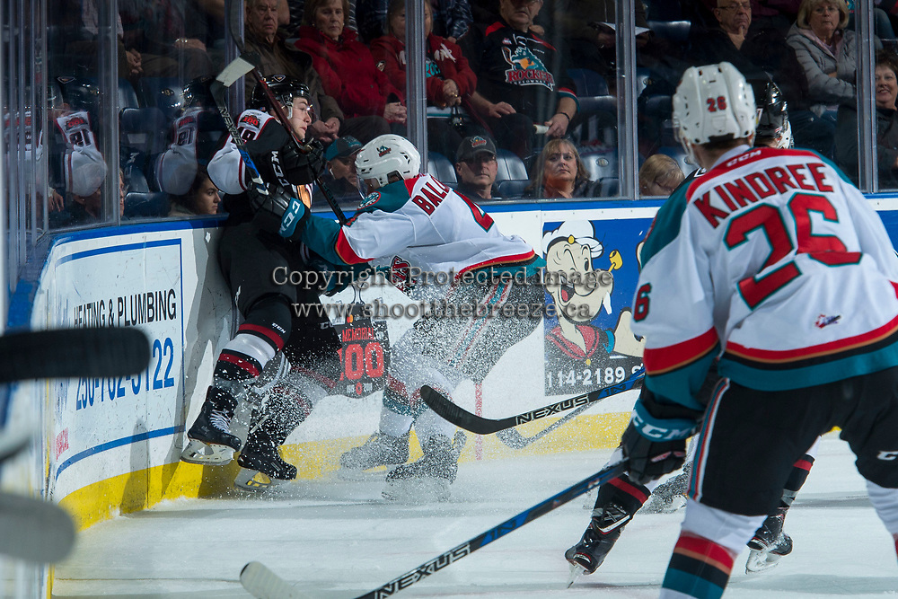 KELOWNA, CANADA - MARCH 7: Gordie Ballhorn #4 of the Kelowna Rockets checks Dawson Holt #19 of the Vancouver Giants into the corner during second period on March 7, 2018 at Prospera Place in Kelowna, British Columbia, Canada.  (Photo by Marissa Baecker/Shoot the Breeze)  *** Local Caption ***